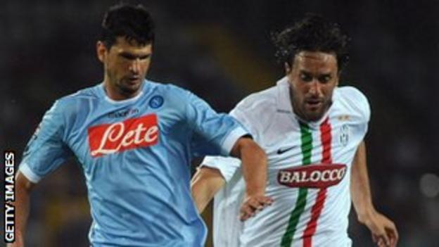 Emilson Cribari is challenged by Luca Toni of Juventus while playing for Napoli