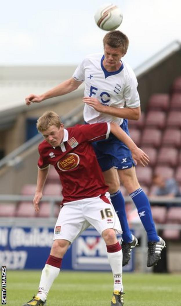 Kerr rises above Northampton Town's Billy McKay during pre-season