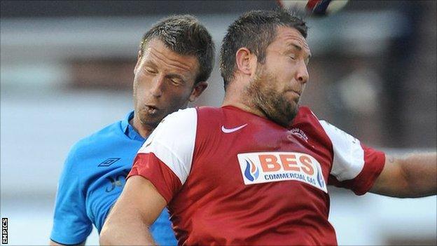 Fleetwood striker Jon Parkin (r) beats Nottingham Forest's Danny Collins to a header