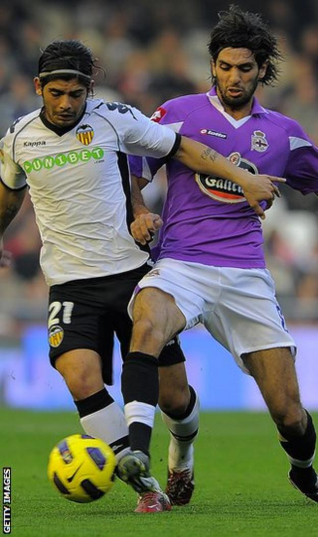 Valencia's Ever Banega holds off Lassad's challenge during their Spanish League game