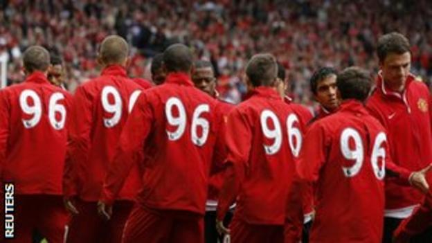 Liverpool players, wearing '96' on their tracksuits, shake hands with Manchester United players before kick-off