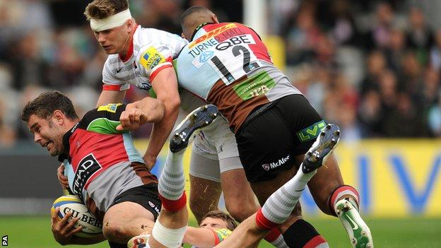 Harlequins number eight Nick Easter is brought to ground as Saracens fly-half Owen Farrell gets involved