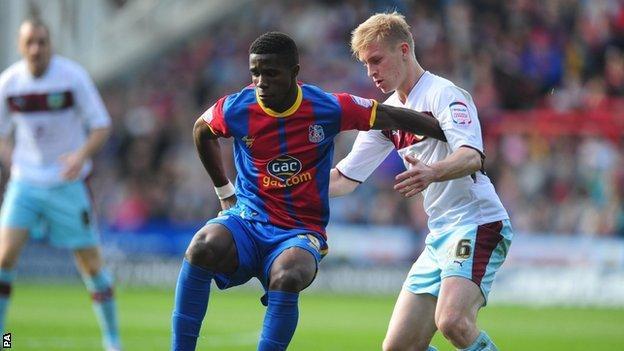 Wilfried Zaha holds off Burnley's Ben Mee