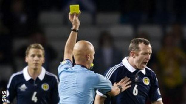 Scotland's Charlie Adam is booked by referee Sergey Karasev