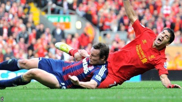 Liverpool's Luis Suarez is challenged by Stoke City's Dean Whitehead (left)
