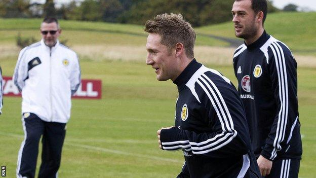 Kris Commons training, with Scotland boss Craig Levein looking on