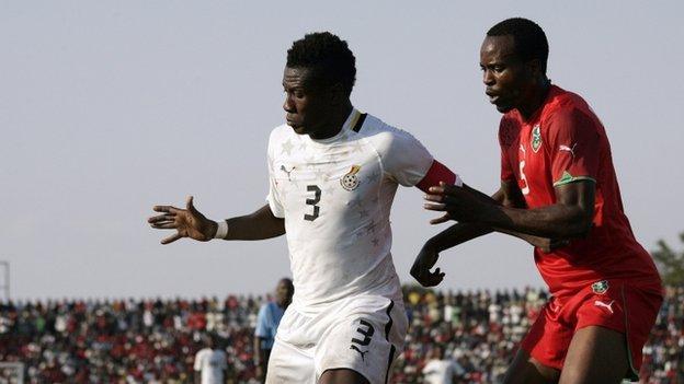 Ghana's Asamoah Gyan (left) battles with Malawi's Foster Namwera