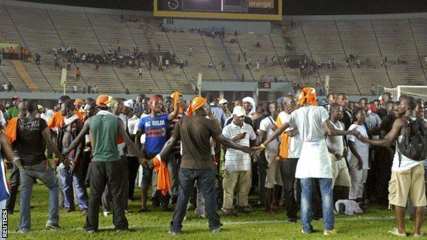 Ivory Coast fans make a ring around each other for safety