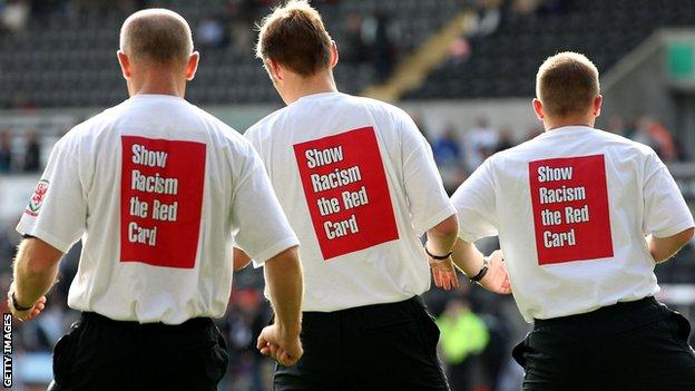 Referee Mike Jones and his assistants warm up with anti racism t-shirts ahead of the Barclays Premier League match between Swansea City and Wigan Athletic at the Liberty Stadium