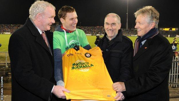 First Minister Peter Robinson and deputy First Minister Martin McGuinness with John McAreavey, husband of Michaela McAreavey, and Tyrone manager Mickey Harte, Michaela's father, at Casement Park