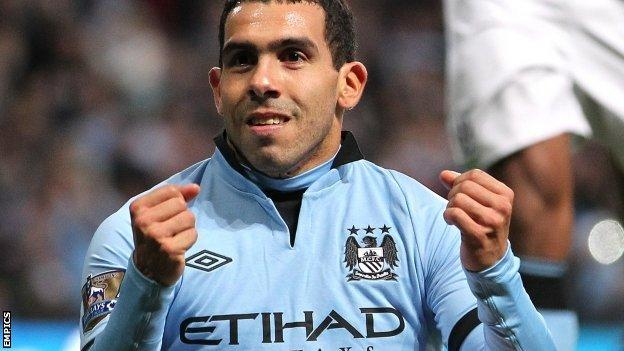 Carlos Tevez celebrates after scoring Manchester City's third goal