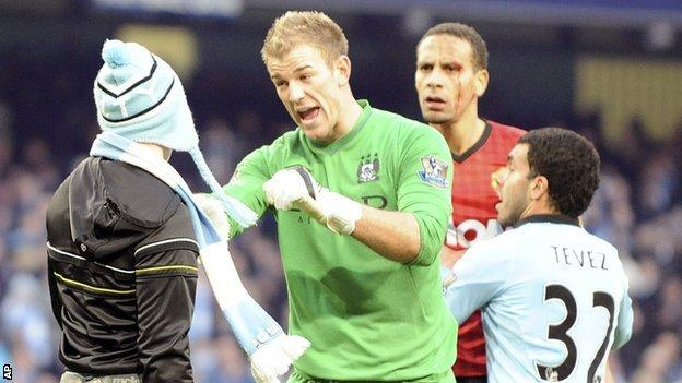 Matthew Stott (left) is stopped from reaching Rio Ferdinand by Joe Hart