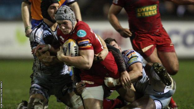 Cardiff Blues' Sam Warburton helps to bring down Scarlet Jonathan Davies in the Pro 12 at Cardiff Arms Park