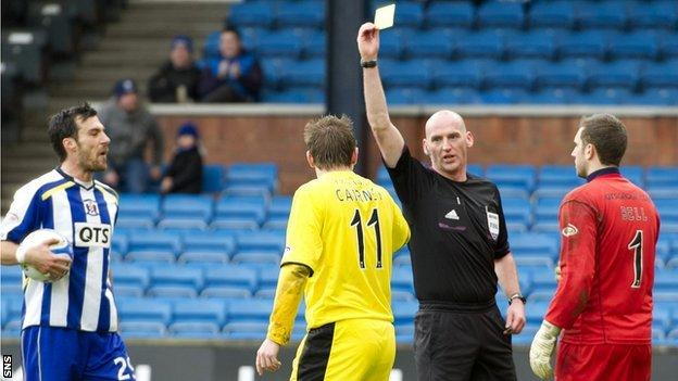 Paul Cairney is booked by Bobby Madden