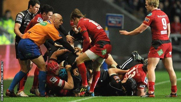 Ospreys and Scarlets players exchange blows