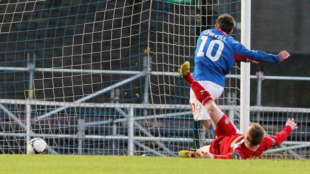 Linfield's Michael Carvill slides the ball into the Cliftonville net to complete a 3-1 win over the Premiership leaders at Windsor Park