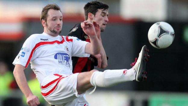 Portadown midfielder Tim Mouncey gets his toe in ahead of Crusaders opponent Declan Caddell at Seaview