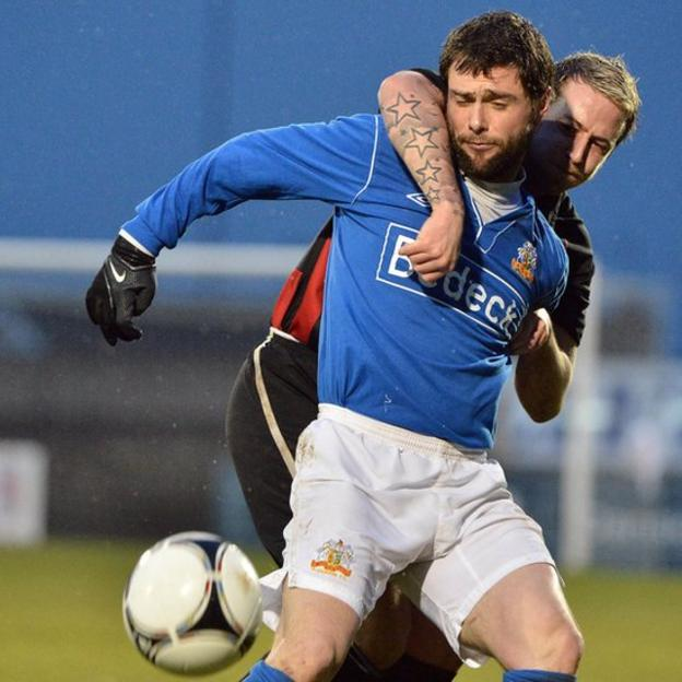 Glenavon player manager Gary Hamilton is closely marked by Crusaders opponent Aiden Watson at Mourneview Park