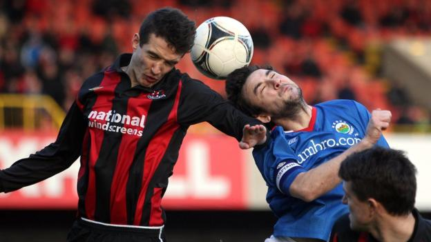 Crusaders midfielder Josh Robinson and Linfield opponent Michael Gault in an aerial duel at Windsor Park
