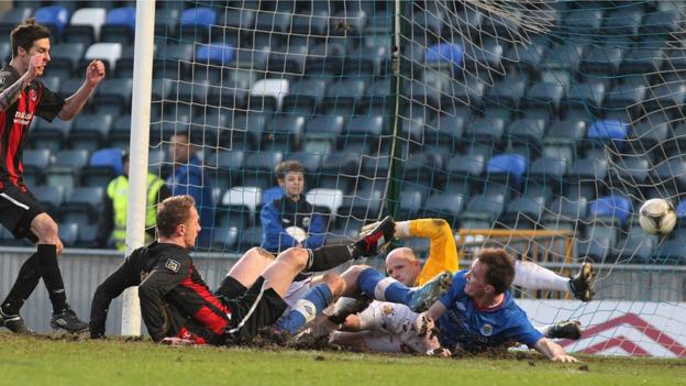 Crusaders striker Timmy Adamson slips to the turf after he scores to secure a 2-2 draw with holders Linfield