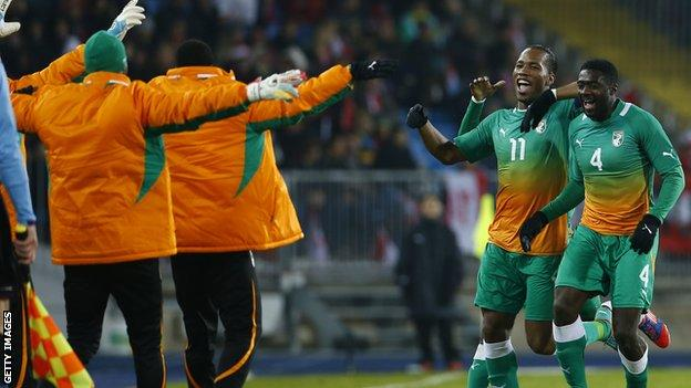 Kolo Toure (R) celebrates with Didier Drogba and team-mates during Ivory Coast's friendly match with Austria in November 2012