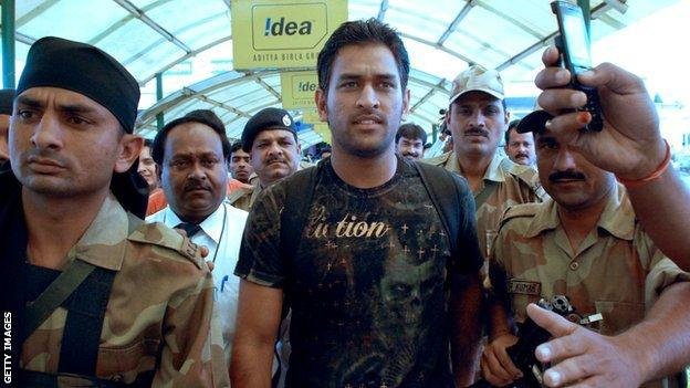Mahendra Dhoni flanked by guards