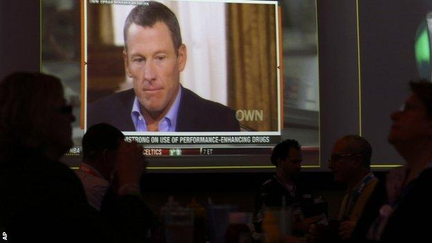 People watch the TV broadcast of Lance Armstrong being interviewed by Oprah Winfrey