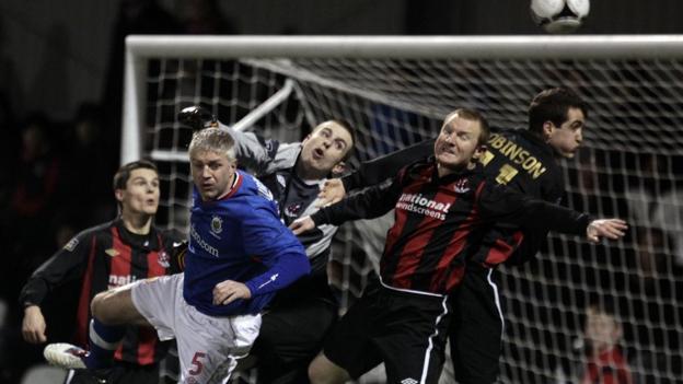 Crusaders debutant goalkeeper Craig Hyland clears from Linfield's William Murphy