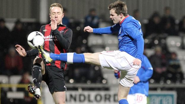 Crusaders striker Timmy Adamson is beaten to the ball by Linfield defender Niall Quinn beats in the Irish Cup fifth round replay at Seaview