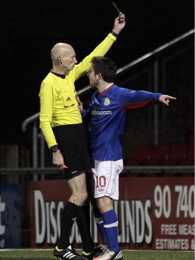 Michael Carvill receives a yellow card for diving from referee Colin Burns following the penalty claim