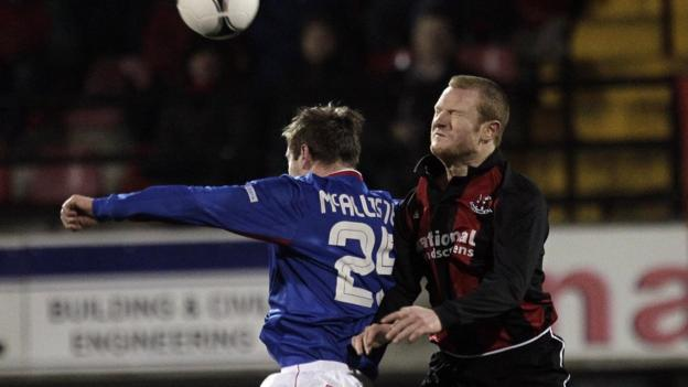 Linfield's Mark McAllister is challenged for the ball by Crusaders defender Davy Magowan