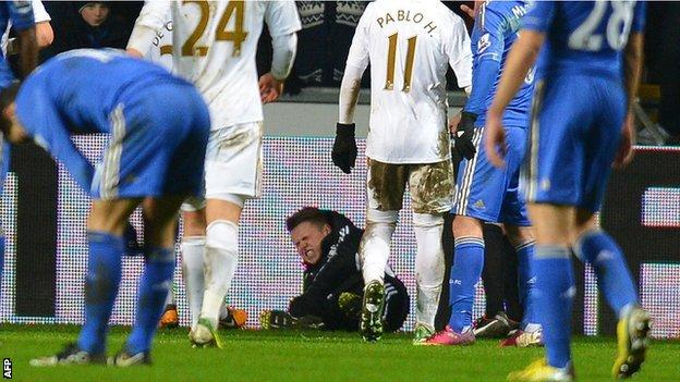 A Swansea ballboy lies on the ground after an altercation with Chelsea midfielder Eden Hazard, who was sent off for his part in the scuffle