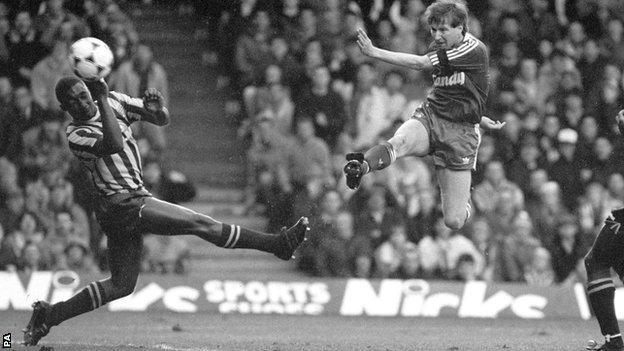 Ronnie Whelan shoots for goal past Brentford defender Roger Stanislaus in the FA Cup quarter-final at Anfield in 1989