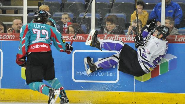 Darryl Lloyd of the Giants sends Kevin Phillips of the Braehead Clan flying in a check during the Elite League game in Belfast