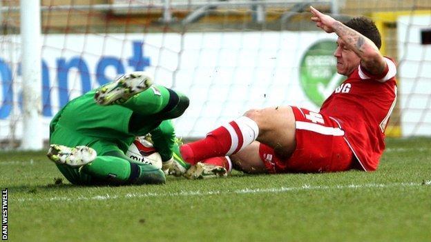 Leyton Orient's Charlie MacDonald slides in on Notts County goalkeeper Bartosz Bialkowski