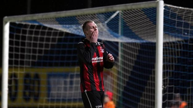 Crusaders forward Jordan Owens misses an early chance in the Windsor Park decider