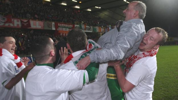 Cliftonville manager Tommy Breslin gets the traditional 'bumps' from his players during the after-match celebrations