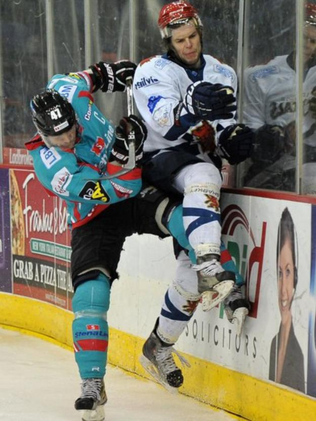 Adam Keefe of the Belfast Giants puts a big check on Michal Benadik of the Edinburgh Capitals