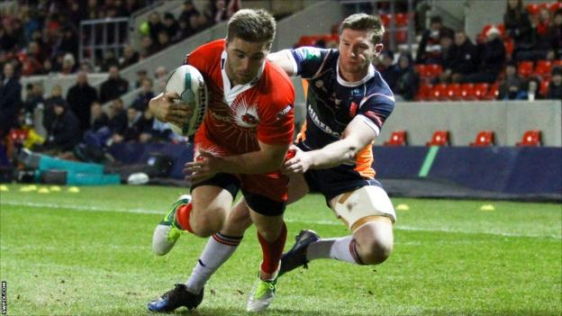 Ashley Gibson slips the tackle of Liam Salter to score for Salford