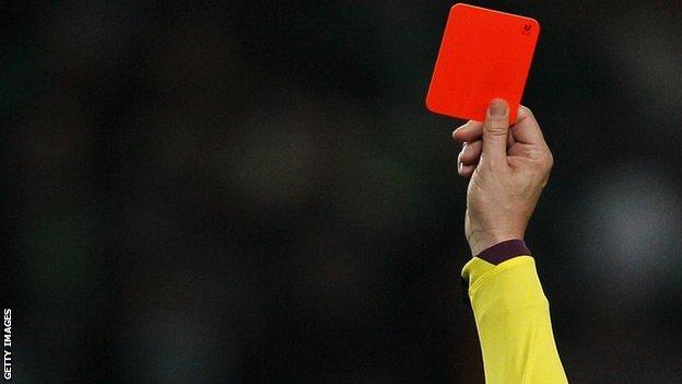 A red card is shown in a football match