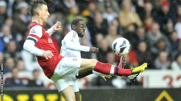 Arsenal's Laurent Koscielny battles for the ball with Swansea winger Nathan Dyer
