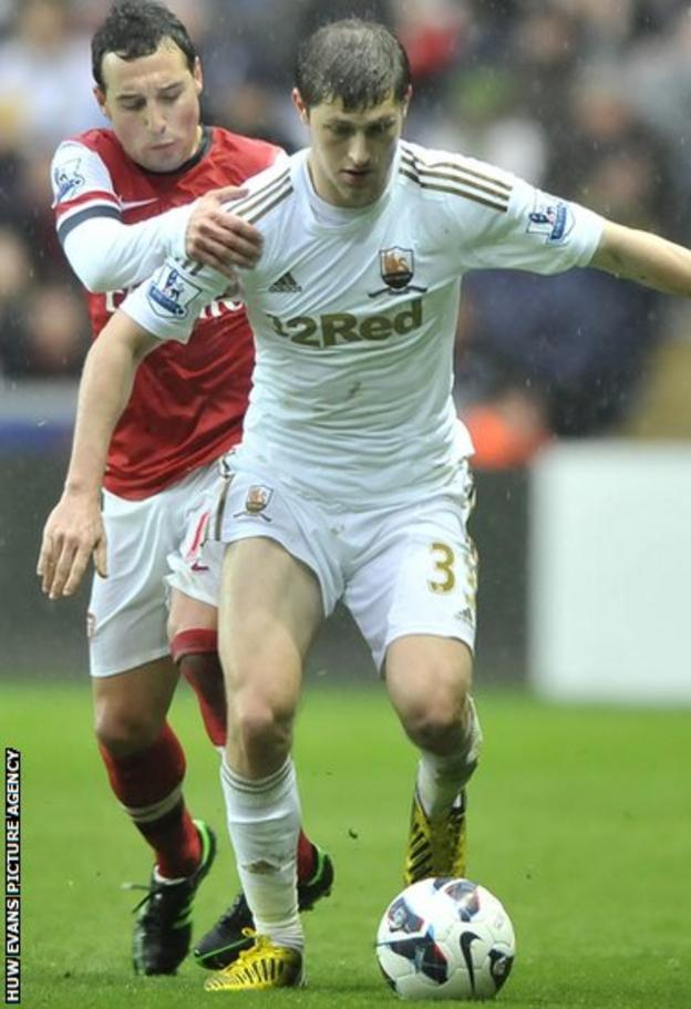Swansea left-back Ben Davies holds off the challenge of Arsenal's Santi Carzola during the Premier League game at the Liberty Stadium.