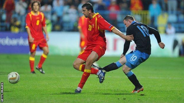 Wayne Rooney of England kicks Miodrag Dzudovic of Montenegro