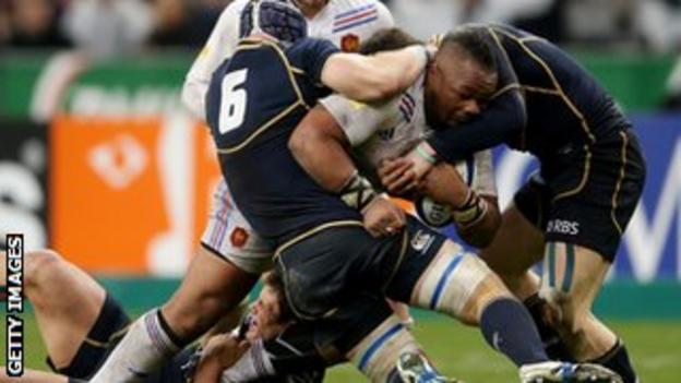 Three Scotland players attempt to stop Mathieu Bastareaud