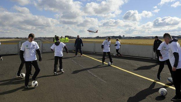 Pupils play football on the runway