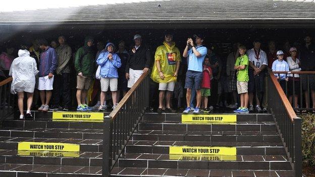 Spectators shelter at the Arnold Palmer Invitational