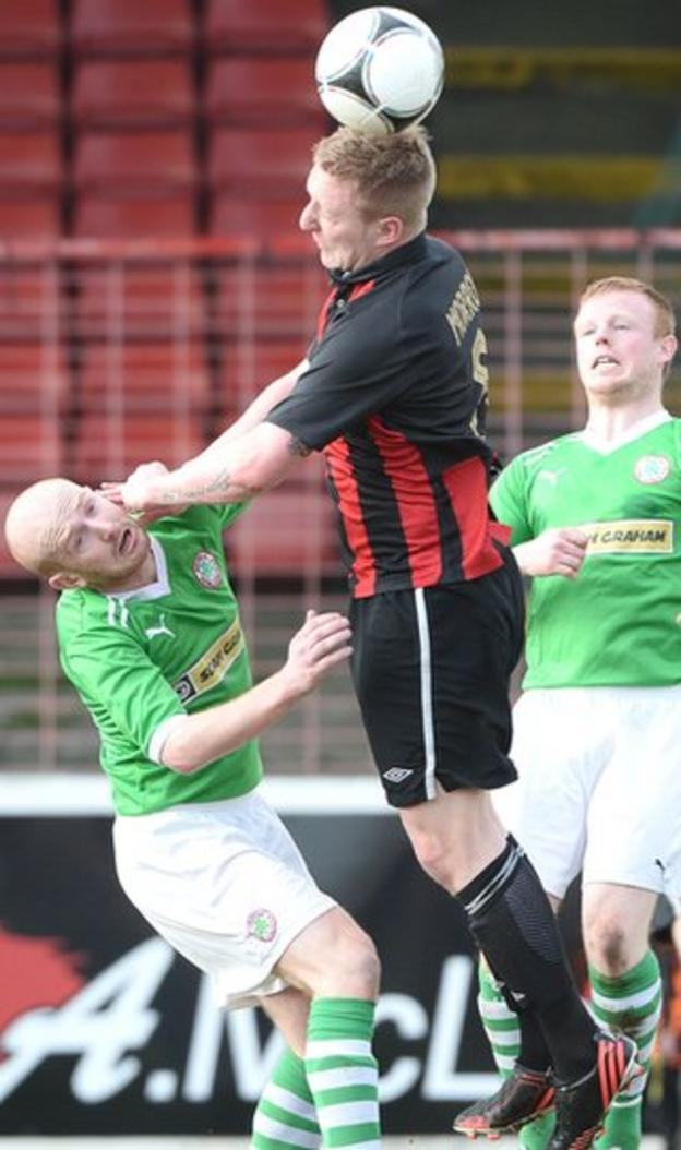 Reds midfielder Ryan Catney is firmly grounded as Chris Morrow rises to head the ball