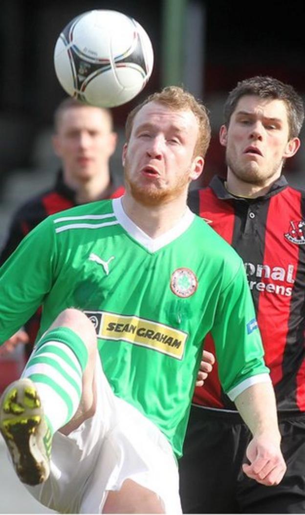 Cliftonville forward Liam Boyce attempts to control the ball as Craig McClean closes in