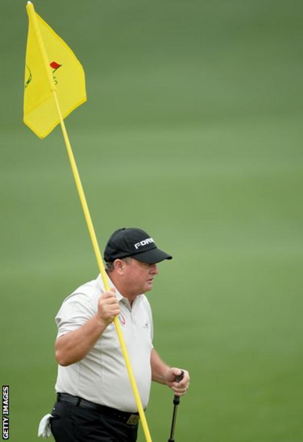The 1991 champion Ian Woosnam holds the flag on the second hole during the first round of the Masters at Augusta.