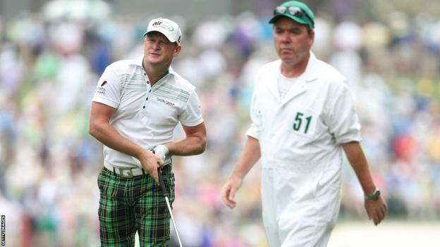 Jamie Donaldson watches his second shot on the first hole as his caddie Michael Donaghy looks on during the first round at Augusta.
